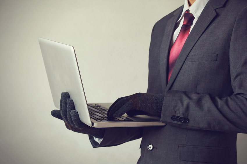 Business man wearing gloves and using computer – fraud, hacker, theft, cyber crime concept